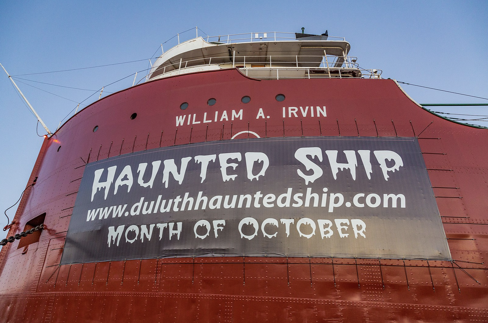 Side of red ship with banner that reads haunted ship