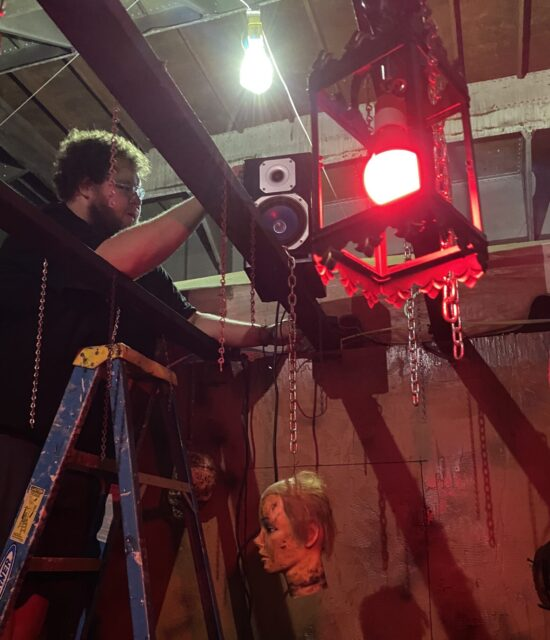 Man on ladder adjusts chain attached to rubber head